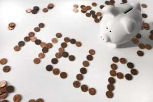 "The word ""HELP"" is spelled out in pennies alongside a white piggy bank."