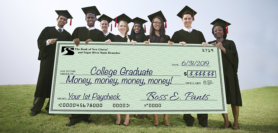 "Several graduates in cap and gown stand together, carrying a large check that representing their first paycheck, made out to ""College Graduate""."